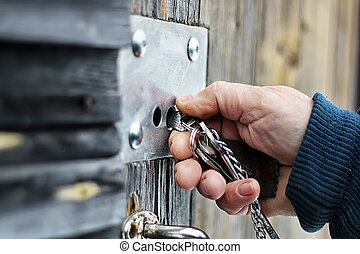hands open padlock - man's hands closed old rusty padlock on...