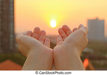 Hands open to the morning sky with the rising sun