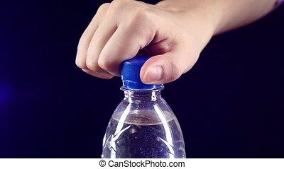 Hands opening a blue bottle of fresh water on dark, slow motion, splash, spray, bubbles