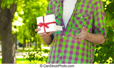 Hands opening gift in park - Closeup hands of guy opening...