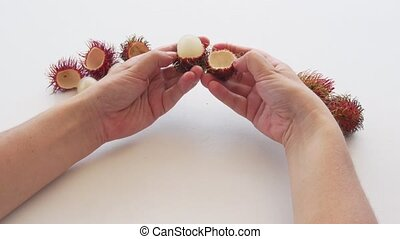 Hands Opening Rambutan Fruit on a White Table. 1080p footage...