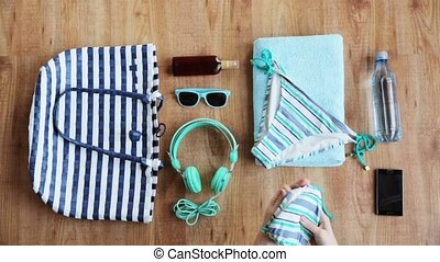 hands packing beach accessories to bag