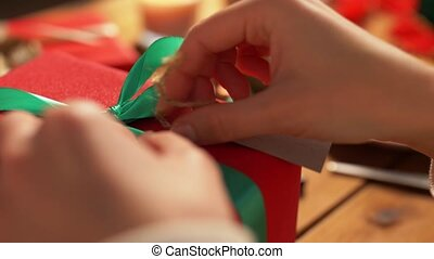 hands packing christmas gift and attaching tag - holidays, ...