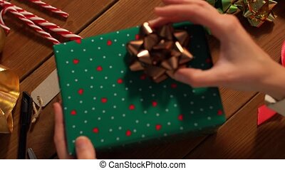 hands packing christmas gift and choosing bow - holidays, ...