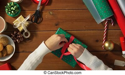 hands packing christmas gift and tying bow - holidays, new ...