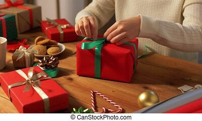 hands packing christmas gift and tying green bow - holidays...
