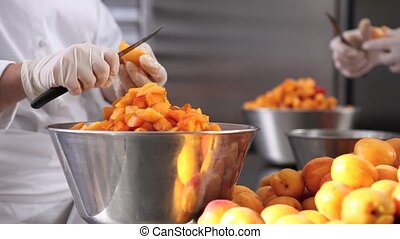 hands pastry chef cutting apricots, prepare the jam in industrial kitchen worktop