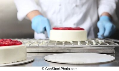 hands pastry chef prepares a cake, cover with icing and...