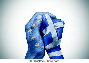 hands patterned with the European and the Greek flag put together