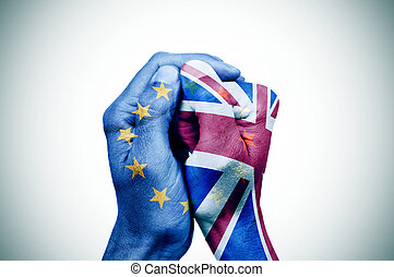 hands patterned with the European and the British flag put...