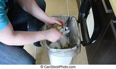 hands peel potatoes. paring fall into recycle bin.