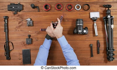 Hands photographer man put the phone on a flexible tripod for selfie. Wooden table top view. Equipment for shooting on the table