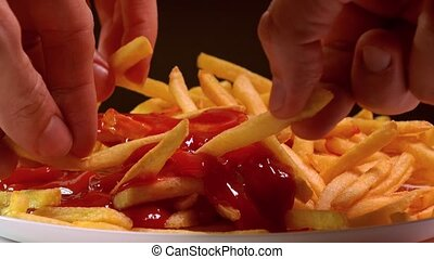 Hands picking fast food french fries and dipping them in...