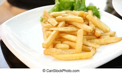 Hands picking fast food fries and dipping them in tomato ketchup. Deep fried potato chips 4K closeup. Slow motion.
