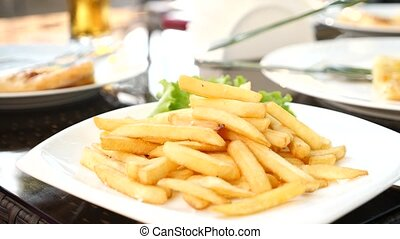 Hands picking fast food fries and dipping them in tomato...
