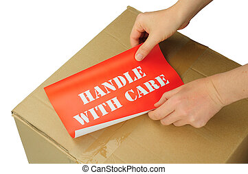 handle with care - hands placing handle with care label on...