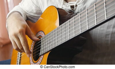 Hands playing on acoustic guitar in slow motion