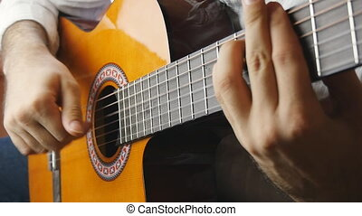 Hands playing on acoustic guitar in slow motion - Male hand...