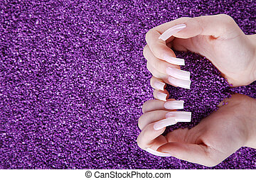 hands playing purple granules