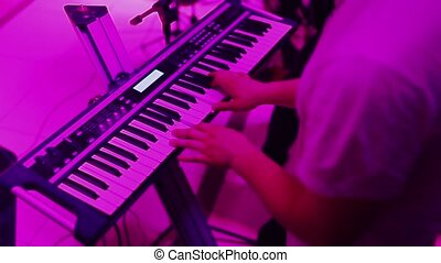 Hands playing the piano. Fingers on the piano, colors lights