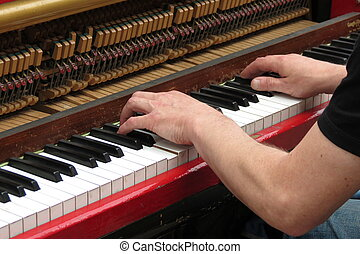 hands playing upright piano