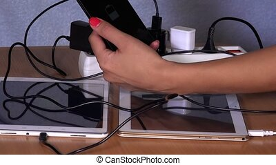hands plug devices charger to extension sockets on table -...