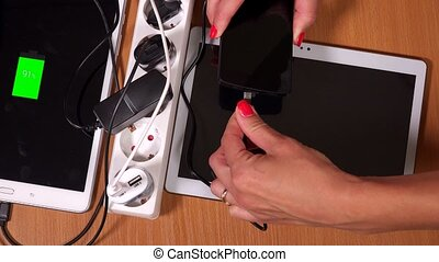 hands plug tablet computers and phones to chargers in...
