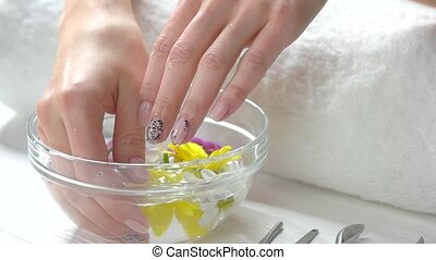 Hands pouring with water in spa salon. Close up female hands...