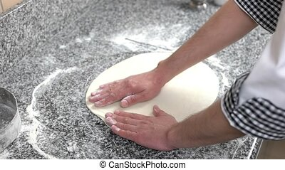 Hands preparing pizza crust. Dough on cooking table.
