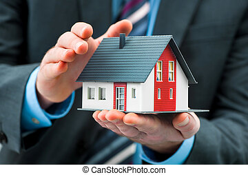 Hands presenting a small house
