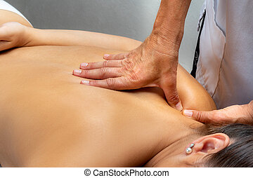 Hands pressing with thumbs on female shoulder.