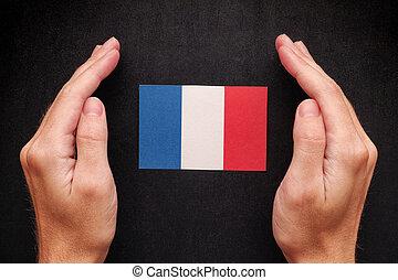Hands protecting Flag of France on black chalkboard background