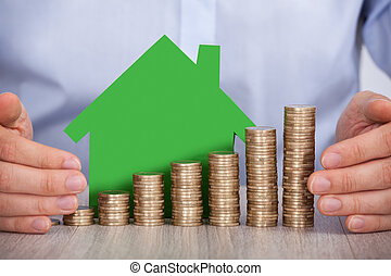 Hands Protecting Stacked Euro Coins And House Model