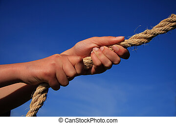 Hands Pulling On Rope - Conceptual image - hands pulling on...