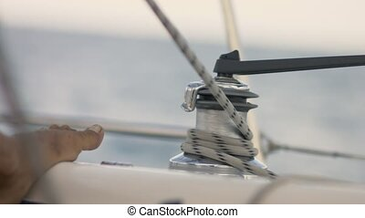 Hands pulling ropes, winding sheets around winches on yacht
