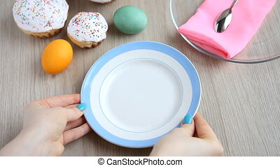 Hands put on the table a plate with a Easter cake with white icing.