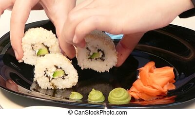 Hands put sushi rolls on a plate