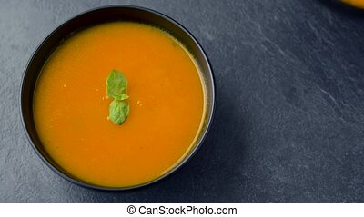hands putting bowl of pumpkin cream soup on table - food,...