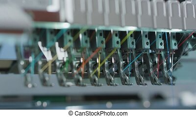 Hands Putting Knit in Needle to Embroidery Machine