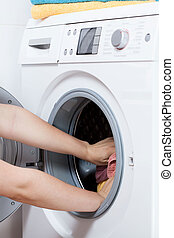 Hands putting laundry into the washing machine drum -...