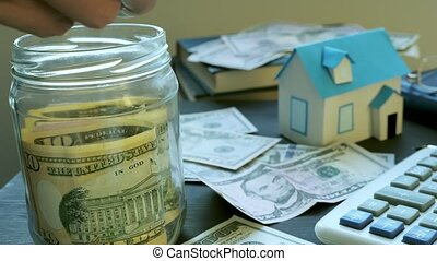 Hands putting money into the jar and model of house. Savings...
