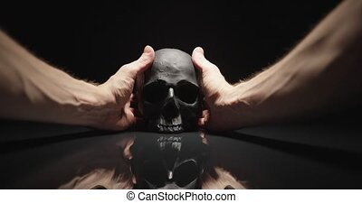 Hands reaching for black skull with reflection angle shot