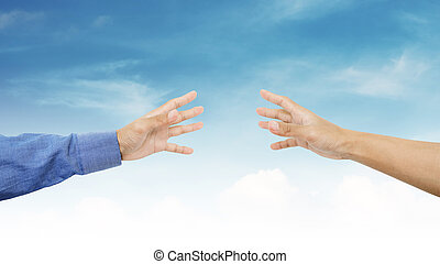 Hands reaching together on blue sky