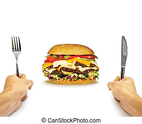 hamburger in front of a man holding fork and knife isolated on white background - man with knife and fork ready to eat burger - diet concept - fast food concept - junk food concept