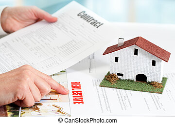 Hands reviewing real estate property documents. - Close up...