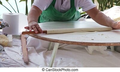 Hands roll the dough - Woman's hands roll the dough on a...