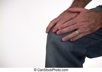 Man rubs sore knee with his hand. Shot on mini DV with a tripod mounted camera.