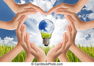 Hands saving , Global Concept of Green Energy Solutions With Light bulb and Planet on Bright Landscape