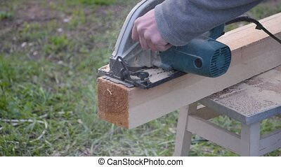 Hands sawing wooden beam lengthwise with a circular hand saw...