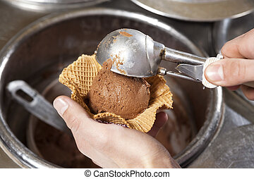 Hands Scooping Ice Cream Into Waffle Bowl At Shop - Closeup...
